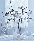 weiße Weihnachten: Zweige in Glasvase dekoriert mit Baumkugeln, Sternanhängern und silbernen Dekovögeln