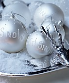 Silver Christmas tree baubles with decorative lettering on silver plate
