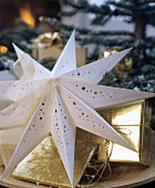 Decorative paper star with perforated pattern and gifts wrapped in gold paper on wooden plate
