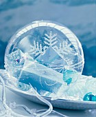 Plexiglas bauble filled with small wrapped gifts on decorative plate