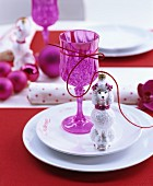 Table festively set in pink with pink baubles and dog-shaped bauble