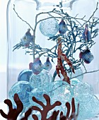 Fairy-tale Christmas arrangement of glass baubles, twigs and fish decorations in glass vase