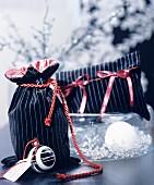 Elegantes Säckchen und Etui aus schwarz-gestreiftem Samtstoff und roten Geschenkbändern