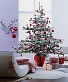 Christmas tree decorated with artificial snow and red baubles