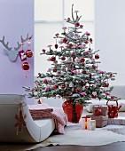 Christbaum dekoriert mit Kunstschnee und rotem Baumschmuck