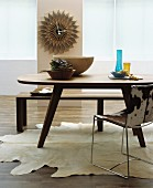 Oval wooden table, bench, metal chair with cowhide cover, cowhide rug and decorative wall clock