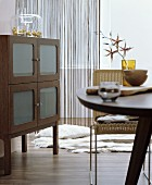 Dining table, wicker chair and sideboard with frosted glass door panels in interior in shades of brown