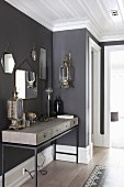 Modern console table with wooden body on metal frames below collection of vintage mirrors on anthracite wall