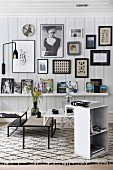Set of coffee tables and small shelving unit on black and white patterned rug with collection of pictures on white wooden wall in background