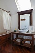 Dark wooden washstand below mirror and skylight next to wood-clad bathtub with shower curtain