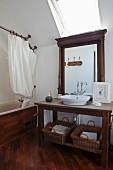 Waschtisch aus dunklem Holz vor Wandspiegel, oberhalb Dachfenster, seitlich eingebaute Badewanne mit Holzverkleidung und Duschvorhang