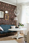 Baroque sofa against floral wallpaper and white coffee table with pedestal base