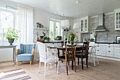 Antique wooden table an various chairs in large country-house kitchen