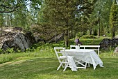 Lace tablecloth on white garden table, bench and chair on lawn with boulders and woods in background