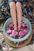 Frau badet Füsse in Wasserschale mit Blüten