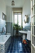 Bathroom with dark blue floor tiles, patterned wall tiles and potted palm on stool below window
