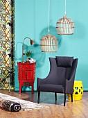 Korbleuchten über grauem Sessel, chinesische Kommode und Hocker vor türkisfarbener Wand
