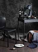 Gothic atmosphere with stylised knight's-helmet lamp, wine, chair and jumble of objects on charcoal-grey table