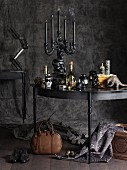 Gothic still-life arrangement with candelabra on table against charcoal-grey background