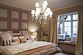 Elegant bedroom in subdued shades of beige with illuminated chandelier and window seat in bay window