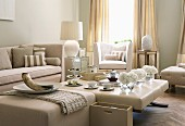 Tea service on ottoman and pale beige seating in traditional living room