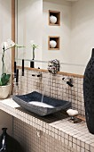 Lion's-head water-spout tap above tiled washstand with dark grey stone basin