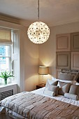 Spherical, crystal chandelier above elegant bed with scatter cushions and bedspread with woven effect