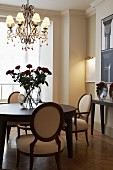 Chandelier above vase of red roses on round dining table and upholstered armchairs with oval backrests