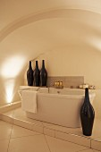 Free-standing bathtub on tiled platform in vaulted niche decorated with artistic vases shaped like bottles