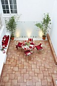 Tiled courtyard with masonry bench and romantically decorated seating area with red cushions