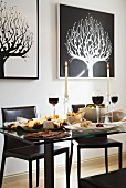 Festively set glass table, black leather chairs and graphical pictures of stylised trees