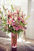 Festive, pink flower arrangement in retro glass vase