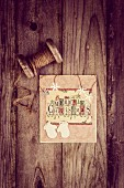 Christmas card and vintage reel of string on rustic wooden surface