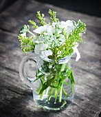 Green stems with buds and white phlox in glass jug on wooden surface