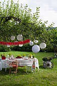 Set table under white lanterns hung from tree for Swedish crayfish-season garden party