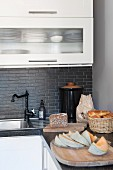 Bread and melon on wooden boards on corner of L-shaped kitchen counter with white cabinet doors and grey stone worksurface