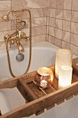 Vintage-style brass tap fittings and candles on bath caddy