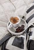 Eine Tasse Cappuccino und Kekse auf einem Marmortablett auf dem Bett