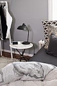 Marble-topped bedside table in bedroom in shades of grey