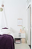Modern bedside cabinet with drawers and purple blanket on bed below suspended globes