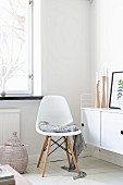 White, classic shell chair on white-painted wooen floor next to sideboard in corner