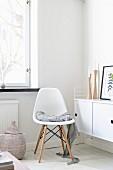 Weisser Schalenstuhl im Klassikerstil auf weiss lackiertem Dielenboden, neben Sideboard in Zimmerecke
