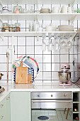 L-shaped kitchen counter with white worksurface below crockery on shelves on white-tiled wall