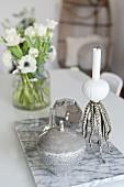 Marmorplatte, Dose und maritimer Kerzenständer auf dem Tisch