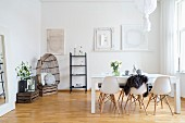 White shell chairs and wine-create accessories in Scandinavian dining room