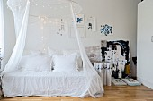 Canopy and fairy lights above romantic daybed with vintage pillows