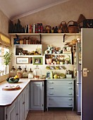 Well-filled, open-fronted, wall-mounted shelves in cosy kitchen