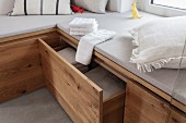 A made-to-measure, upholstered wooden corner bench with drawers for towels in a spa bathroom