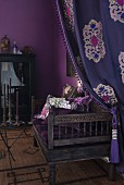 Draped curtain and antique bench with patterned scatter cushions in corner of room painted aubergine