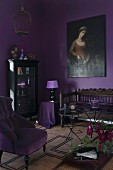 Room in shades of purple: armchair with mauve cover and antique bench below oil painting on wall painted aubergine